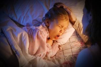 девочка лежит в постели и кашляет