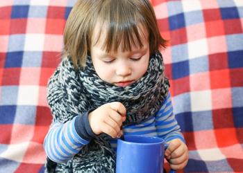 ребенок в шерстяном шарфе с кружкой